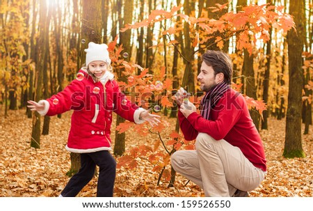 Smiling, cheerful father and daughter blowing soap bubbles and having fun outdoor in an autumn park - happy active caucasian family in nature - stock photo