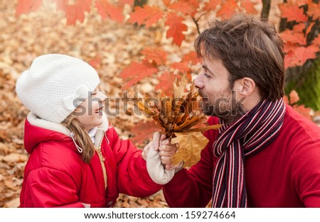 Smiling, cheerful father and daughter having fun outdoor in the park during autumn - close up portrait of happy loving active caucasian family in nature - stock photo