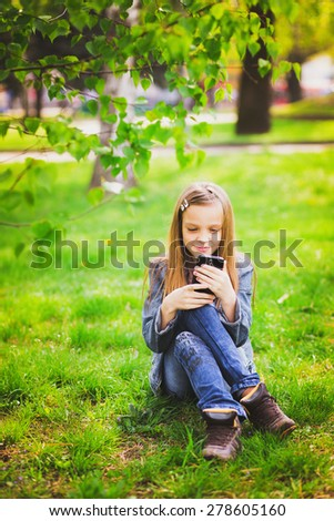 smiling cheerful girl sitting in urban park and texting sms using smart phone - stock photo