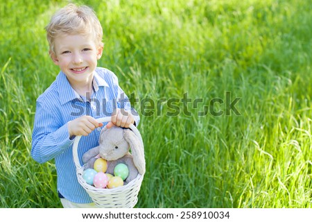 smiling cheerful little boy holding basket with colorful easter eggs and bunny toy at spring time in the park - stock photo
