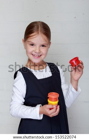 Smiling cheerful little girl in school uniform holding a tube of paint for art school