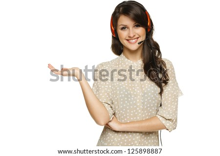 Smiling cheerful woman in headset holding empty copy space on her open palm, looking at camera, isolated on white background