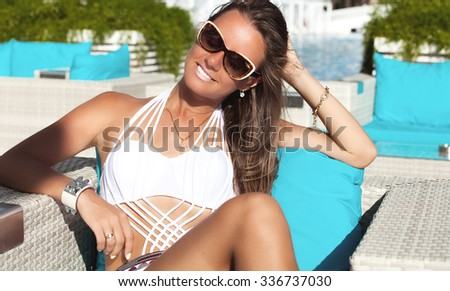 Smiling cheerful woman sitting near swimming pool in luxurious hotel. Woman relaxing enjoying luxury lifestyle outdoor day dreaming. Summer luxury vacation. - stock photo