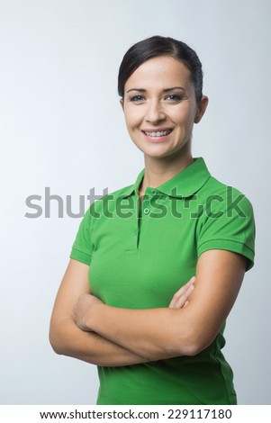 Smiling cheerful young woman in green polo t-shirt with arms crossed. - stock photo