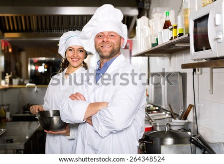 Smiling  chef and cook  working  in restaurant kitchen - stock photo