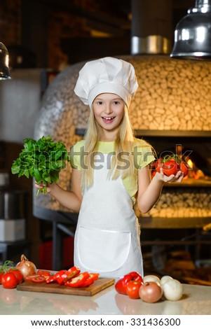 Smiling Chef girl preparing healthy food vegetable salad at restaurant kitchen - stock photo