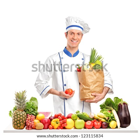 Smiling chef holding a tomato and paper bag behind a table full of fruits and vegetables isolated on white background - stock photo