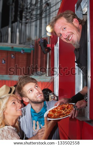 Smiling Chef holding pizza with teenage couple