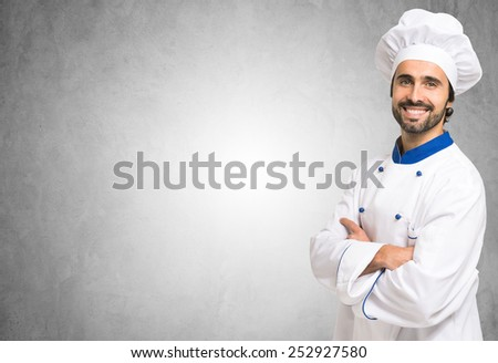 Smiling chef in front of a blank wall. Lots of copyspace - stock photo