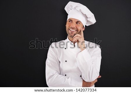 Smiling chef looking on the side - stock photo