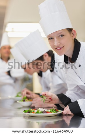Smiling chef looking up from preparing salad in culinary class - stock photo