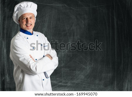 Smiling chef posing against a blackboard - stock photo