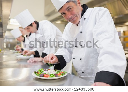 Smiling Chef's preparing their salads in the kitchen - stock photo