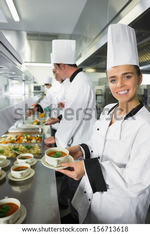Smiling chef showing her soup in a busy kitchen - stock photo