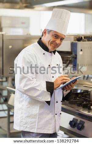 Smiling chef using digital tablet in the kitchen