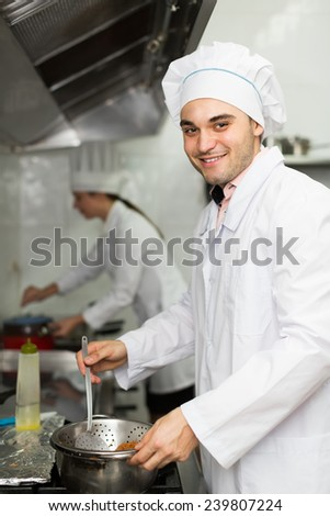 Smiling chef with assistant cooking at professional kitchen in the restaurant. Focus on man