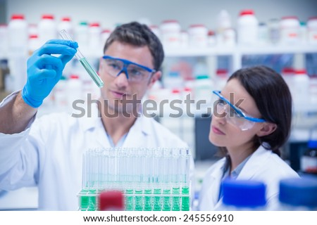 Smiling chemist holding test tube containing liquid in the laboratory - stock photo
