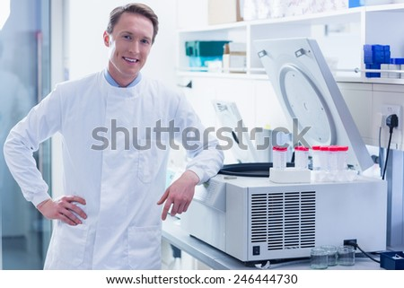 Smiling chemist leaning against the centrifuge in laboratory - stock photo