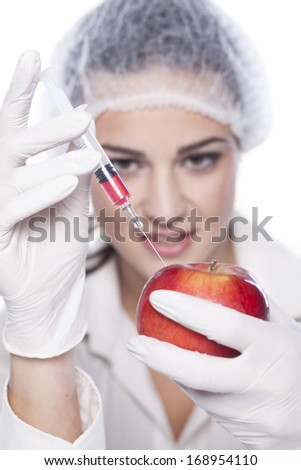 smiling chemist woman injected some liquid in red apple