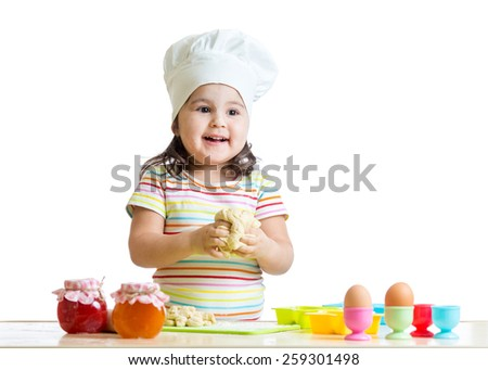 smiling chid toddler girl kneading dough in kitchen - stock photo