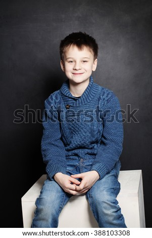 Smiling Child Boy in Blue Sweater on Dark Background - stock photo