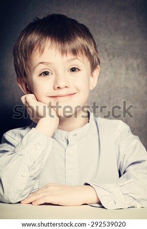 Smiling Child Boy Sits at a School Desk - stock photo