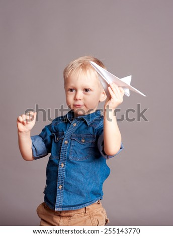 Smiling child boy 3-4 year old playing with origami plane in room. Wearing trendy clothes over gray. Childhood. - stock photo