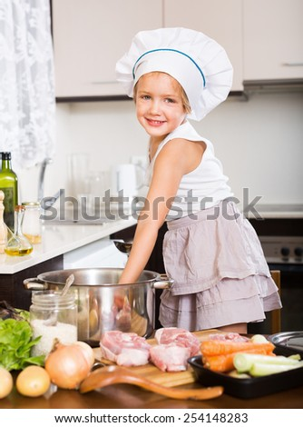 Smiling child cooking soup at kitchen