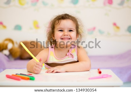 smiling child drawing with felt-tip pen - stock photo