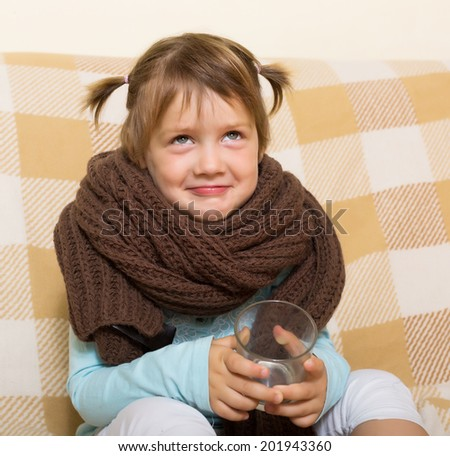 Smiling child dressed in warm  scarf drinking from glass   - stock photo