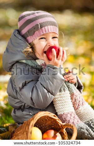 Smiling child eating red apple in autumn park. Healthy lifestyles concept - stock photo