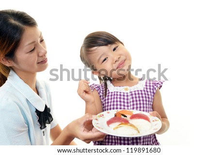 smiling child eating sushi - stock photo
