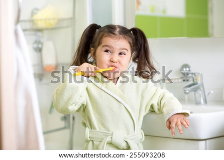 Smiling child girl brushing teeth in bathroom - stock photo