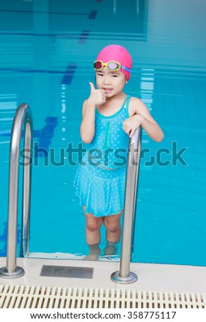 Smiling child girl swim in a blue pool
