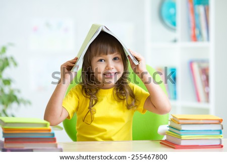smiling child girl with a book over her head in primary school - stock photo