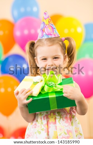 smiling child girl with gidts on birthday party - stock photo