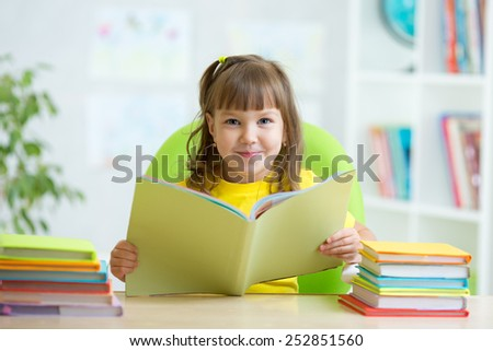 smiling child girl with opened book at table - stock photo