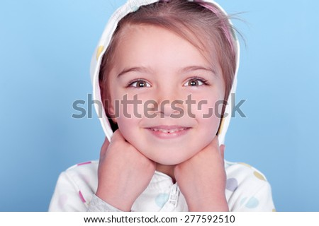 Smiling child girl 3-4 year old wearing hoodie over blue. Looking at camera Childhood. Happiness. Cheerful.  - stock photo