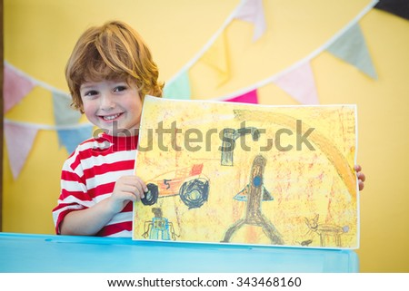 Smiling child holding up his finished painting at the desk - stock photo