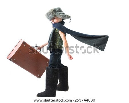 Smiling child in a fur hat and felt boots purposefully moving forward with developing scarf and holds old suitcase in his hand on a white background - stock photo