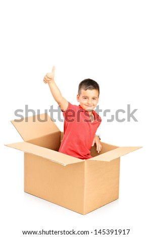 Smiling child in a paper box giving thumb up and looking at camera, isolated on white background