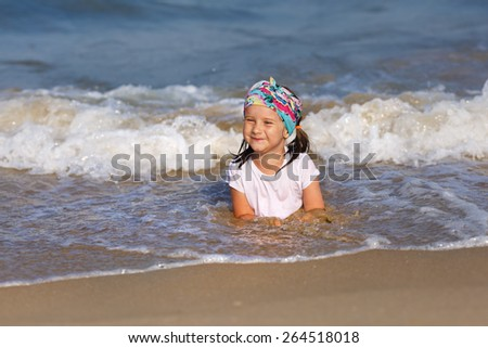 Smiling child in a white t-shirt lying in water on the beach. Shallow depth of field. Focus on the model's face. - stock photo