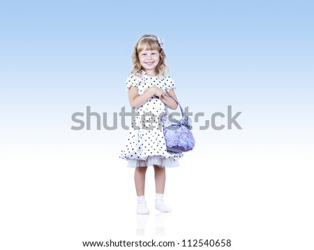 Smiling child in dress with handbag under sky