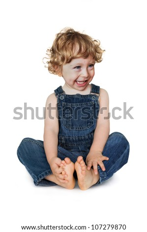 Smiling child in jeans sitting