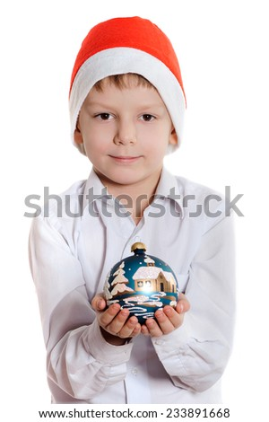 Smiling child in Santa red hat holding Christmas ball in hands. Christmas concept. - stock photo