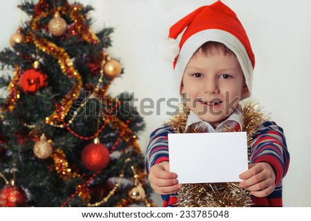 Smiling child in Santa red hat holding Christmas greeting blank card in hands. Christmas concept. Selective focus - stock photo