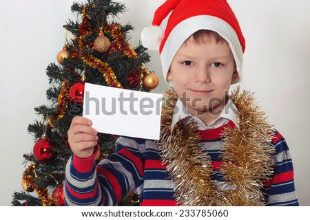 Smiling child in Santa red hat holding Christmas greeting blank card in hands. Christmas concept. - stock photo