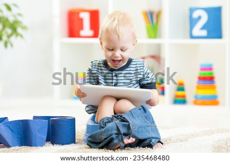 smiling child sitting on chamber pot with toilet paper rolls - stock photo