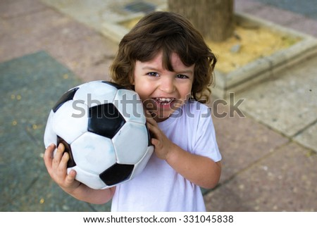 Smiling child with a soccer ball in his hands - stock photo