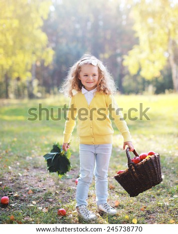 Smiling child with autumn basket having fun outdoors in warm sunny day - stock photo